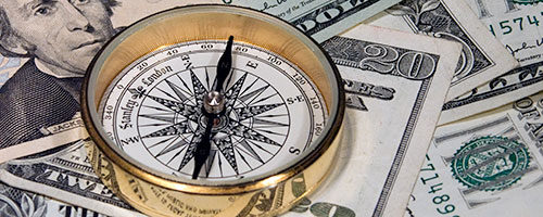 compass on top of money