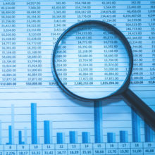 Magnifying glass on charts and data | forensic accounting, fraud examination, business valuation