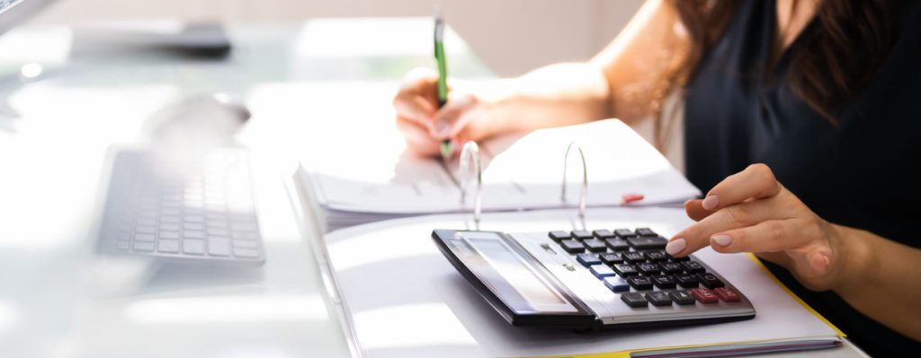 woman typing on calculator and taking notes